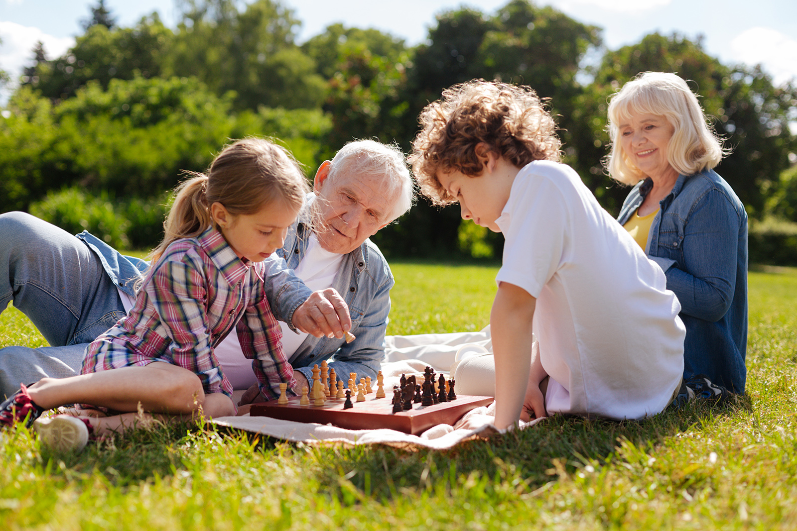 Grandparents sitting in the grass playing chess with their grandchildren
